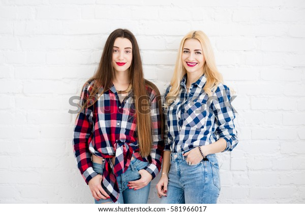 Female friends in checkered shirts and jeans standing together on the white wall background