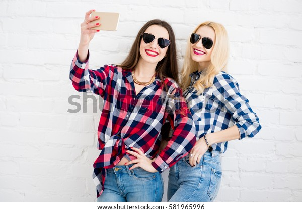 Female friends in checkered shirts making selfie portrait with phone on the white wall background