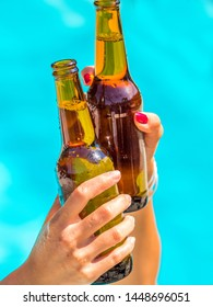 Female friends cheer clinking bottles of beer in their hands next to a pool of blue water