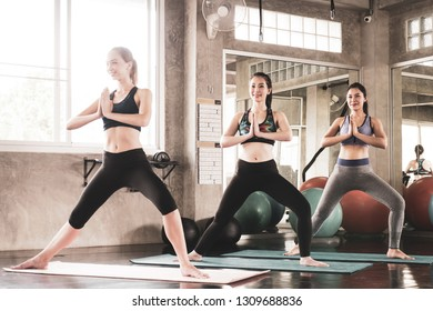 Female friends are doing yoga exercise together at the gym.
