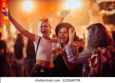 Female friends drinking beer and having fun at music festival