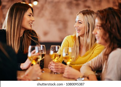 Female friends drinking wine and chatting while sitting in the bar.