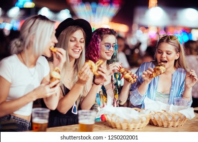 Female friends eating and drinking at music festival