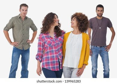 Female friends embracing with two males standing in background on white background