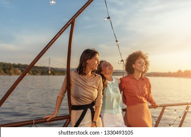 Female friends enjoying the breeze while cruising on the river