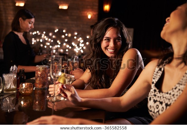 Female Friends Enjoying Night Out At Cocktail Bar