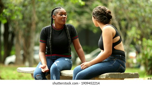 Female friends gossiping and talking interaction outside at park bench