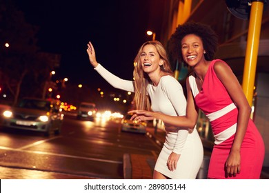 Female friends hailing taxi on city street at night