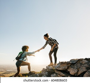 Female friends hiking help each other in mountains. Young female hiker helping friend while trekking in mountain.