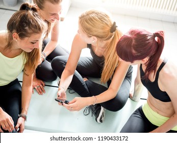 female friends in locker room of the gym relaxing looking at a smartphone and chatting