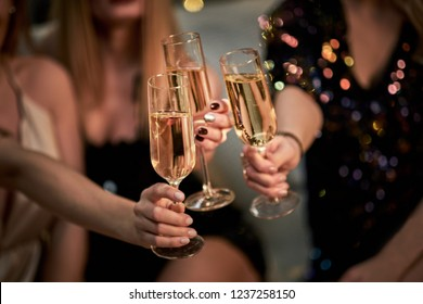 Female Friends Make Toast As They Celebrate At Party. Group of partying girls clinking flutes with sparkling wine