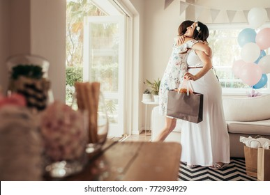 Female friends meeting for baby shower at home. Woman hugging expecting mother at baby shower.