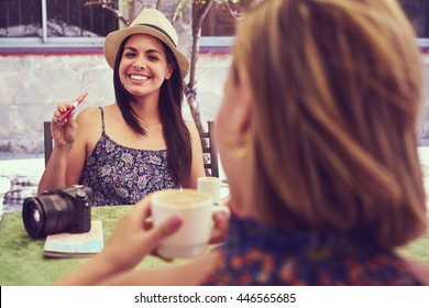 Female friends on holidays, young happy women sitting at bar smoking electronic cigarette.