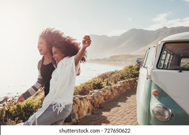 Female friends on road trip enjoying outdoors on a sunny day. Women standing outside van  and laughing.