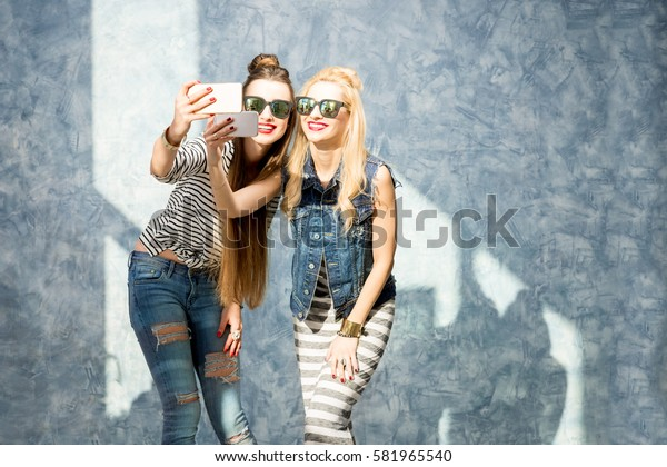Female friends photographing with phones standing on the blue wall background