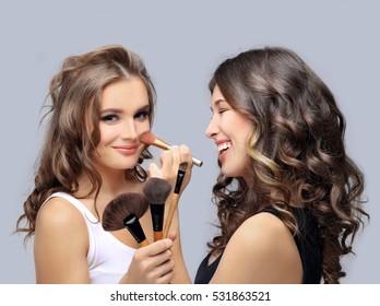 Female friends putting makeup