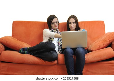female friends relax and working on  laptop computer at home on orange sofa isolated on white backgrond