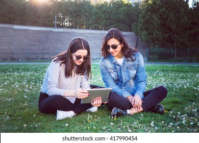 Female friends share common experience with touchscreen tablet computer at park