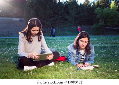 Female friends spend time together with touchscreen tablet computer at park