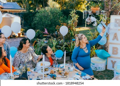 Female friends taking selfie with pregnant woman at a baby shower. Mobile photography, party decorations in white and blue colors, baby boy