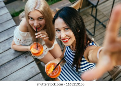 Female friends taking selpfie photos loking at camera and enjoying fresh drinks. Top view of girls toasting each other with aperol spritz cocktails at the wooden table.
