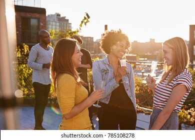 Female friends talking at a rooftop party, backlit