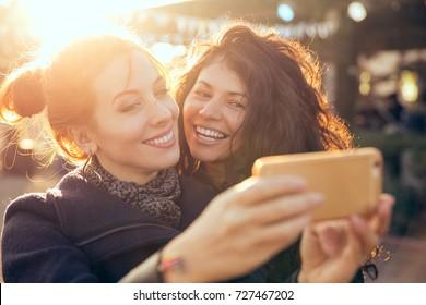 Female friends two women taking selfie during weekend getaway Outdoors
