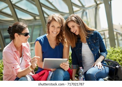 Female friends using tablet computer outdoors, smiling happy.