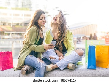 Female friends watching something funny on a smartphone - Girlfriends laughing and having fun outdoors