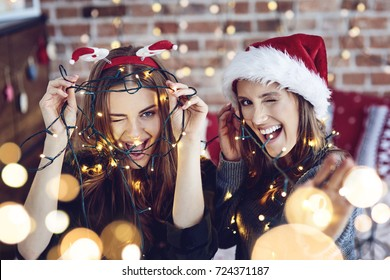 Female friends winking and laughing