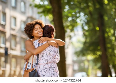 female friendship, people and leisure - young women or friends hugging at summer park