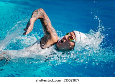 Female front crawl swimmer with tattoos  during training