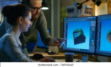 Female Game Developer Has Discussion with Male Project Manager While Working on a Game Level on Her Personal Computer with Two Displays. They Work in a Modern Loft Office Creative Environment.