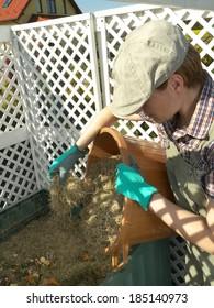 Female gardener dumping cut lawn grass into green plastic compost bin