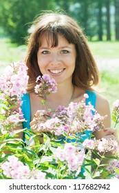 Female gardener in phlox plant at garden