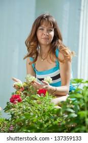 Female gardener in roses plant at garden