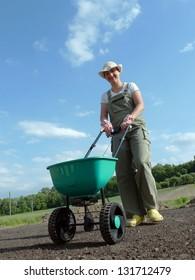 Female gardener spreading grass seeds using seeder