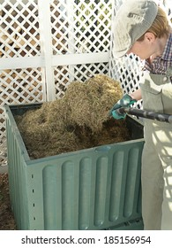 Female gardener turning over compost bin content using pitchfork to speed up decomposting process