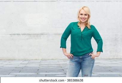 female, gender, portrait, plus size and people concept - smiling young woman in shirt and jeans over gray concrete wall background