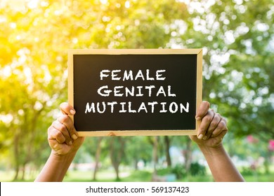 FEMALE GENITAL MUTILATION write on black board with hand hold the board