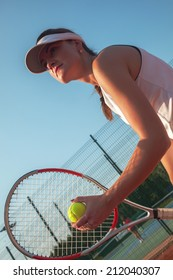 Female Getting Ready To Serve On A Tennis Court