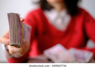 Female giving money banknotes for a payment. Beautiful woman in red paying salaries to workers. Maybe she is a loan shark. Selective focused on money.