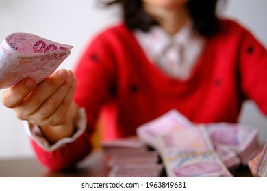 Female giving only one money banknote for a payment. Beautiful woman in red paying salaries to workers.Selective focused on money.