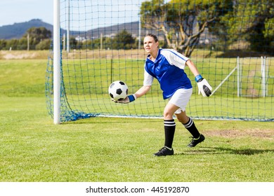 Female goalkeeper about to throw a football in field