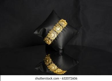 female Golden Eastern Turkish vintage women's handmade jewelry on a black background. bracelets,