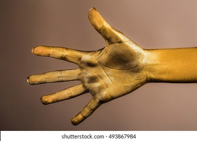 female golden or gold hand or arm with palm and fingers with body art painted metallized color on grey background, closeup