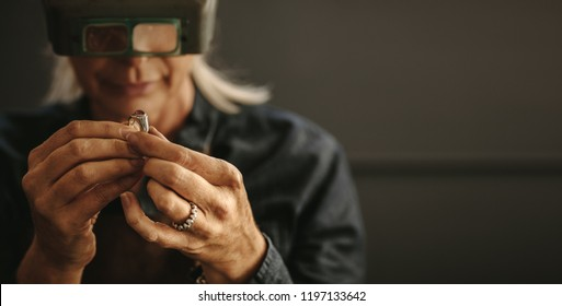 Female goldsmith inspecting jewelry using magnifying glass in workshop.  Woman jeweler inspecting diamond ring with magnifying glass.