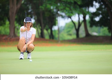 Female golf player with putter squatting to analyze the green at golf course