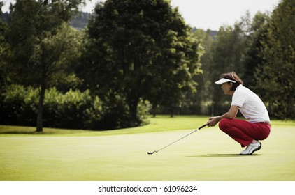 Female golf player with putter squatting to study the green at golf course.