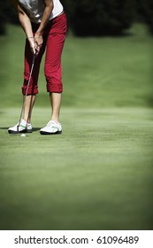 Female golf player putting with ball just dropping into hole, with plenty of copy-space.
